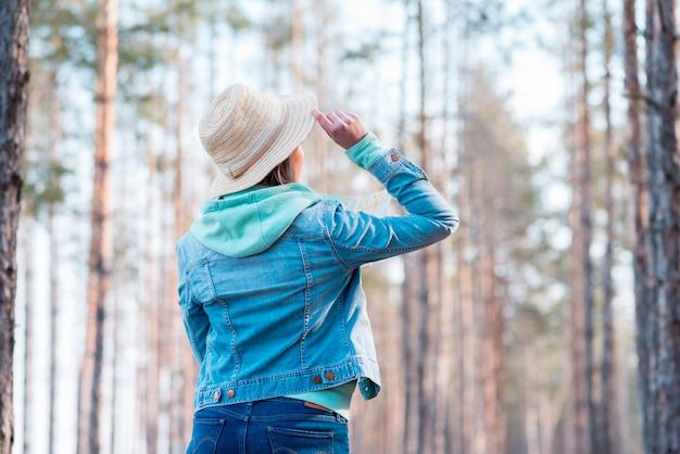 Hintere ansicht eines tragenden hutes der frau auf dem kopf, der bäume im wald betrachtet Kostenlose Fotos