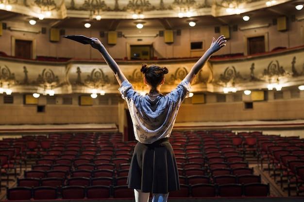 Hintere ansicht eines weiblichen pantomimen, der ihre arme anhebt Premium Fotos