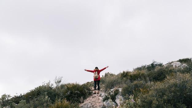 Hintere ansicht eines weiblichen wanderers, der auf der gebirgsoberseite steht, die ihre hände ausstreckt Kostenlose Fotos