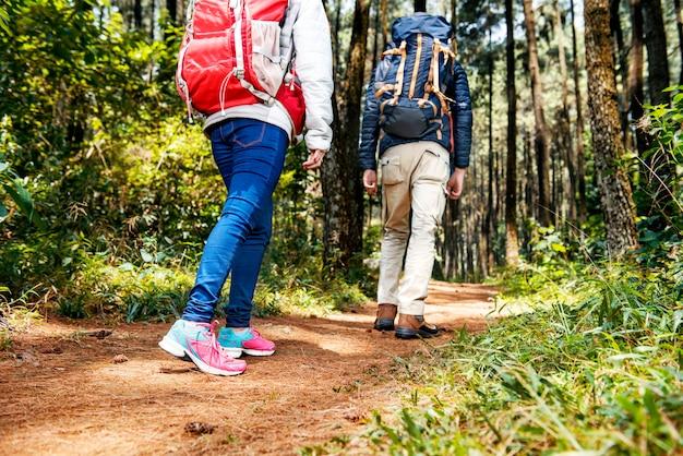 Hintere ansicht von asiatischen wandererpaaren mit rucksack unten gehend Premium Fotos