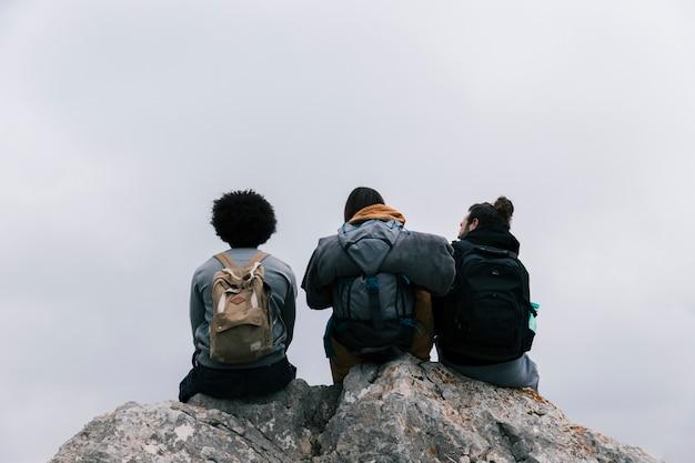 Hintere ansicht von drei freunden, die auf felsen gegen himmel sitzen Kostenlose Fotos