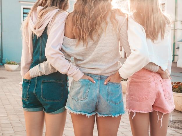 Hintere ansicht von drei jungen weiblichen hippie-freunden mädchen gekleidet in der zufälligen kleidung des sommers frauen, die draußen stehen sie setzten ihre hände kurz gesagt in gesäßtaschen ein aufstellung bei sonnenuntergang Kostenlose Fotos