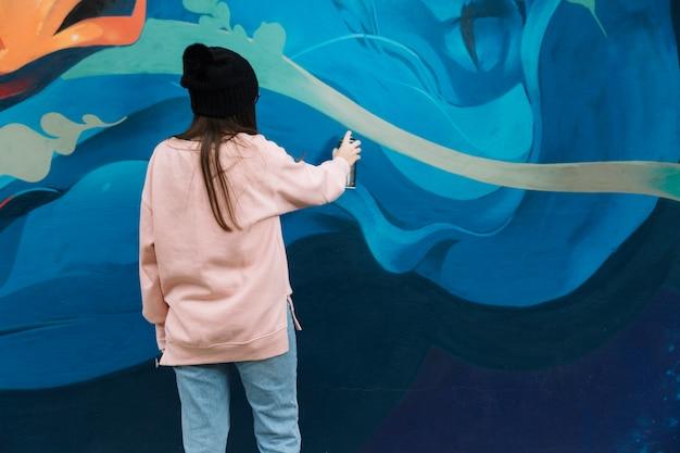 Hintere ansicht von frauenhandzeichnungsgraffiti mit sprühfarbe Kostenlose Fotos