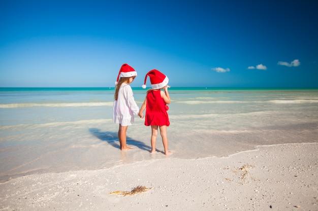 Hintere ansicht von kleinen netten mädchen in den weihnachtshüten auf dem exotischen strand Premium Fotos