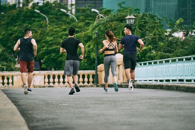 Hintere ansicht von mann drei und von mädchen, die zusammen an einem sommertag rütteln Kostenlose Fotos