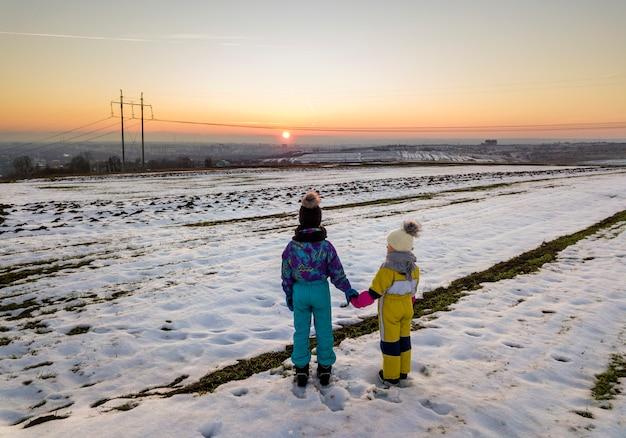 Hintere ansicht von zwei kleinen kindern in warmer kleidung, die im gefrorenen schneefeld händchenhalten auf kopienraumhintergrund der untergehenden sonne und des klaren blauen himmels stehen. Premium Fotos
