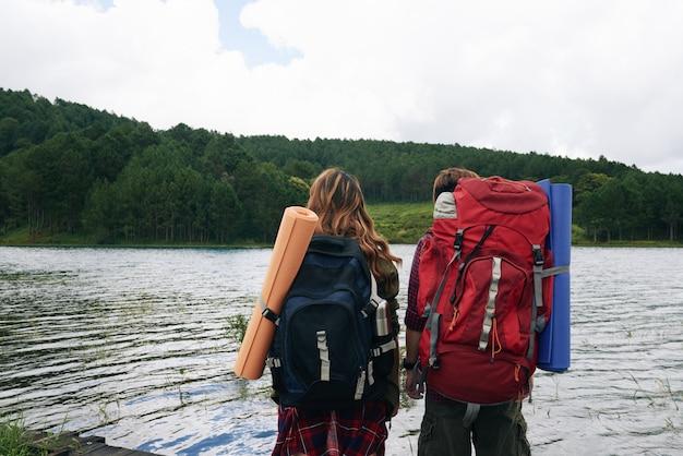 Hintere ansicht von zwei wanderern mit den rucksäcken, die wasser gegenüberstellen Kostenlose Fotos