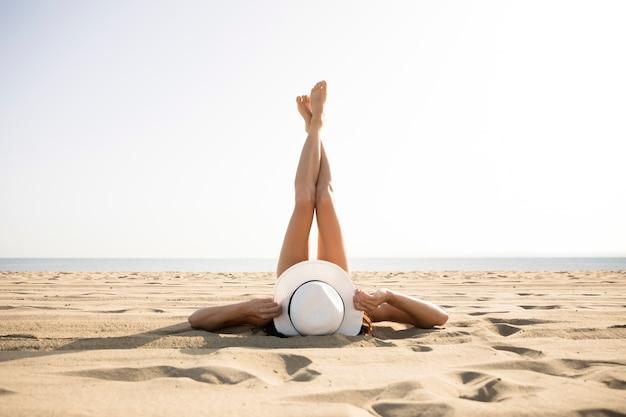 Hintere ansichtfrau auf strand mit den füßen oben Kostenlose Fotos