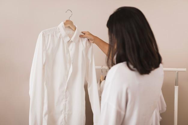 Hintere ansichtfrau, die ein weißes hemd betrachtet Kostenlose Fotos
