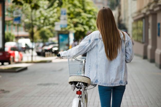 Hintere ansichtfrau, die nahe bei fahrrad geht Kostenlose Fotos