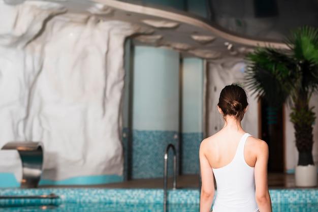 Hinteres ansichtmädchen, das in badeanzug aufwirft Kostenlose Fotos