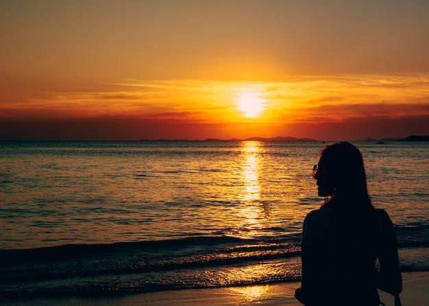 Hinteres ansichtporträt einer einsamen frau mit sonnenbrille am strandsonnenuntergang. Premium Fotos