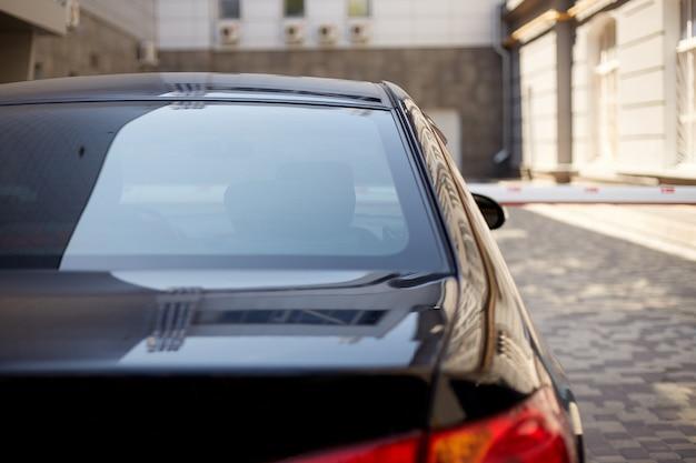 Hinteres fenster des schwarzen autos geparkt auf der straße im sonnigen sommertag, rückansicht. modell für aufkleber oder abziehbilder Premium Fotos