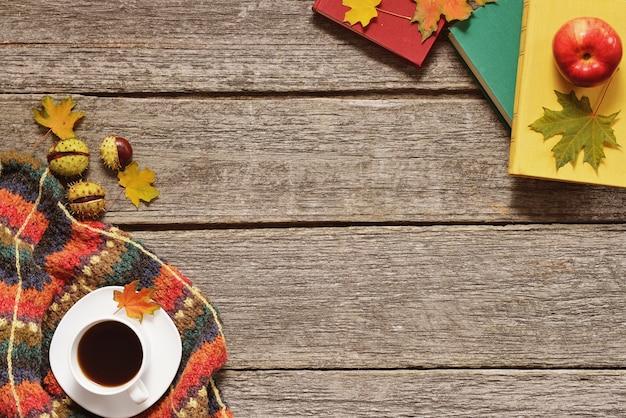 Hintergrund der roten, grünen und gelben blätter des herbstes, der äpfel mit tasse kaffee oder des tees mit büchern Premium Fotos