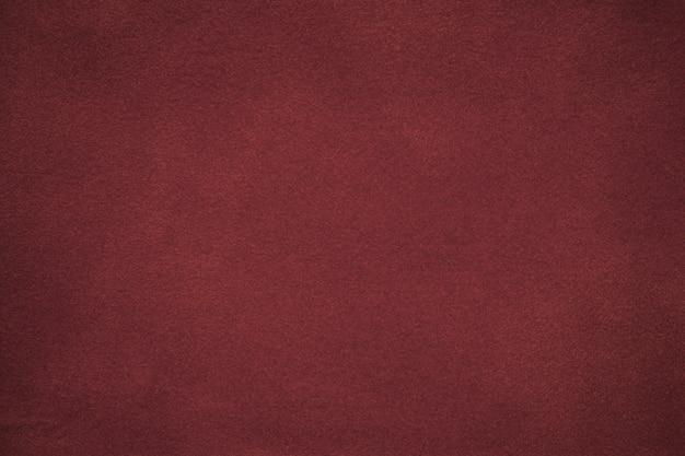 Hintergrund des dunkelroten veloursledergewebes Premium Fotos
