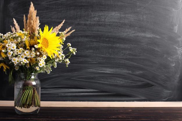 Hintergrund des lehrertages. leerer kopienraum des schwarzen kreidebrettes und frische wildflowers im vase. Premium Fotos