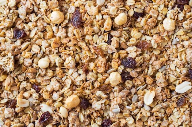 Hintergrund des müsli-frühstücks mit hafer blättert rosinen ab. Premium Fotos