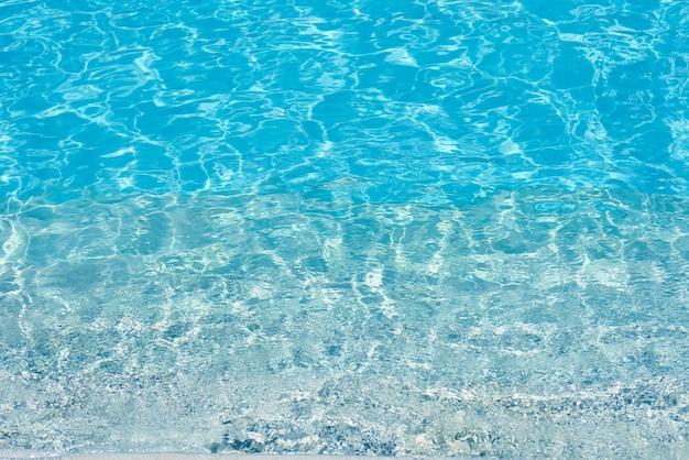 Hintergrund des wassers im blauen swimmingpool, wasseroberfläche mit einer sonnenreflexion Premium Fotos