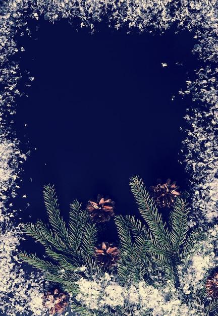 Hintergrund für neujahrsgrüße mit ästen, zapfen und schnee Premium Fotos