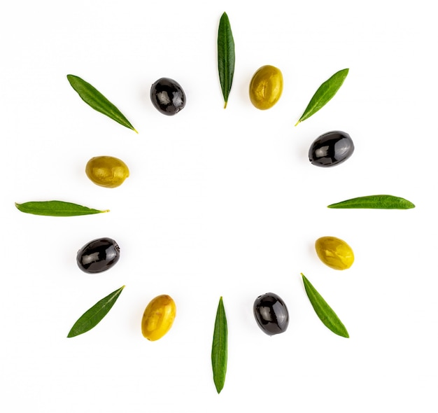 Hintergrund mit grünen und schwarzen oliven und mit olivenblättern. lokalisierter raum, zum ihres textes hier einzufügen. Premium Fotos