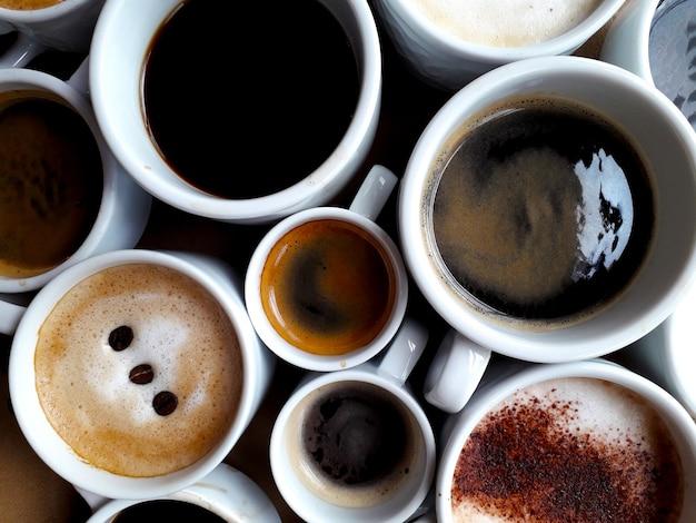 Hintergrund mit mehreren tassen verschiedenen kaffeesorten von oben Premium Fotos