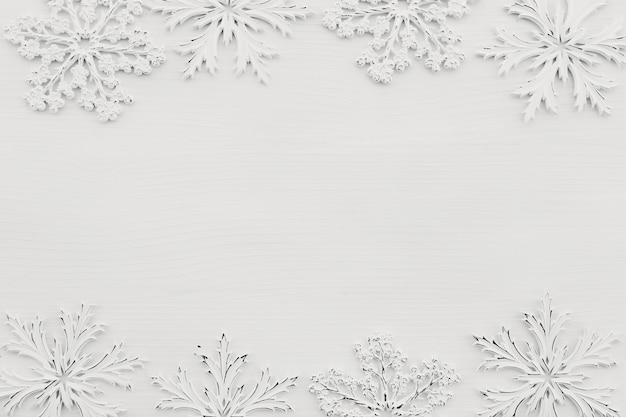 Hintergrund mit weißen schneeflocken auf weißem holz Premium Fotos