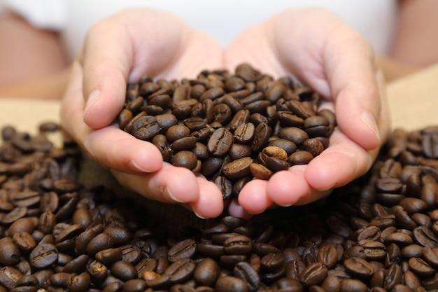Hintergrund von den röstkaffeebohnen, die aus schalenförmigen händen in einen leinwandsack heraus gießen Premium Fotos