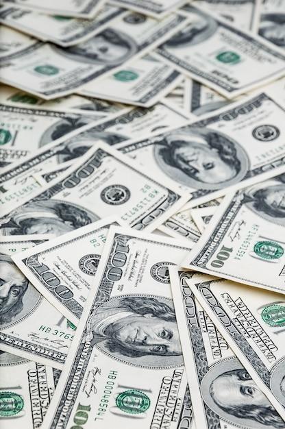 Hintergrund von dollar. noten von einhundert us-dollar sind im hintergrund verstreut. Premium Fotos