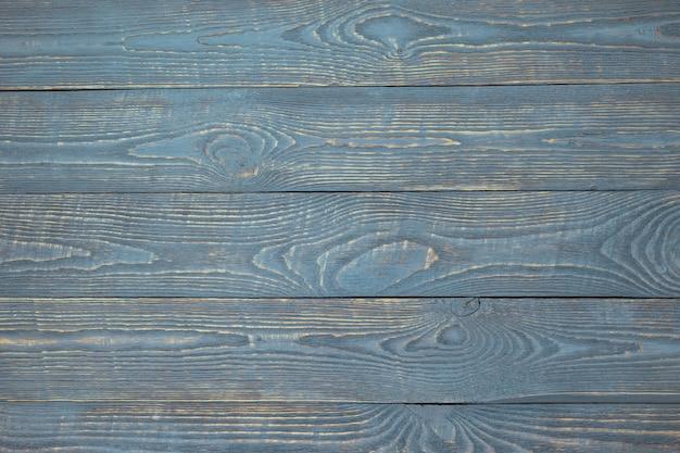 Hintergrund von hölzernen beschaffenheitsbrettern mit resten der hellblauen farbe. horizontal. Premium Fotos