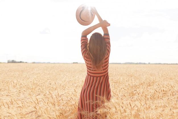Hintergrundansicht einer schlanken, gut geformten frau, die ihre arme hochhält, einen strohhut in einer hand hat, vor der sonne mit vergnügen in der mitte des weizenfeldes steht und die sommerferien in der ländlichen gegend genießt. Kostenlose Fotos