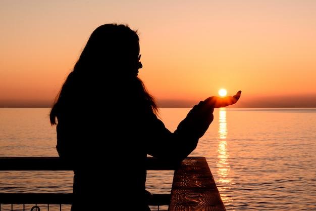 Hintergrundbeleuchtetes mädchen während eines sonnenaufgangs, der die sonne mit ihren händen fängt Premium Fotos