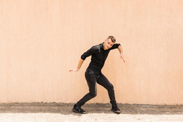 Hip-hop tanzen des jungen mannes gegen beige wand Kostenlose Fotos