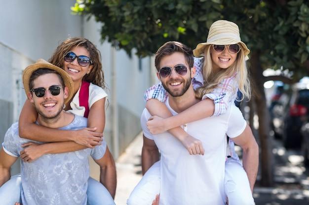 Hippe männer, die ihren freundinnen auf der straße huckepack geben Premium Fotos