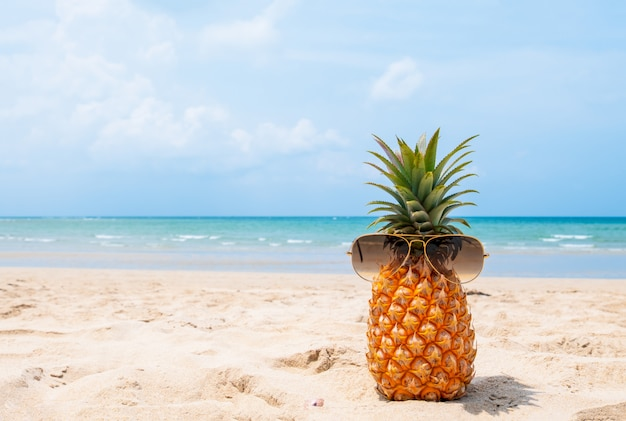 Hippie-ananas mit sonnenbrille auf tropischem strand. Premium Fotos