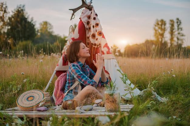 Hippie-frau in form eines schamanen sucht inspiration von mutter erde in einem wigwam in der natur. Premium Fotos