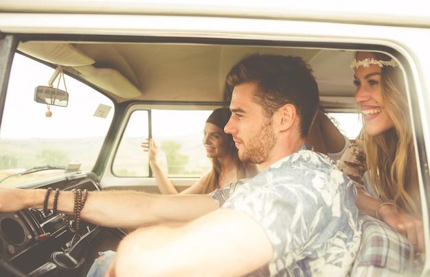 Hippie-freunde fahren auf einem minivan Premium Fotos