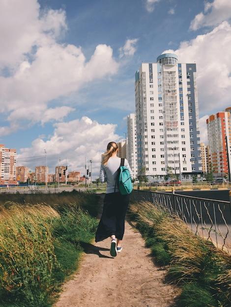 Hippie-mädchen mit einem rucksack ist auf der straße Premium Fotos