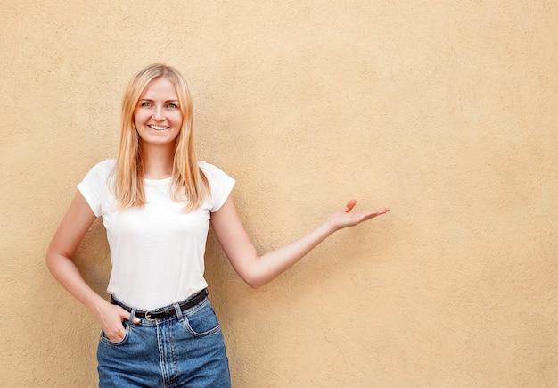 Hippie-mädchen, welches das leere weiße t-shirt und jeans aufwerfen gegen raue straßenwand, unbedeutende städtische kleidungsart, frau trägt, stellt eigenhändig dar Premium Fotos