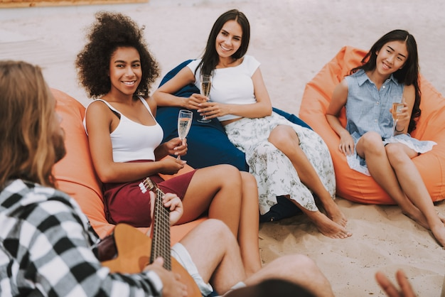 Hippie-mann, der gitarre auf dem strand-mädchen-lächeln spielt Premium Fotos