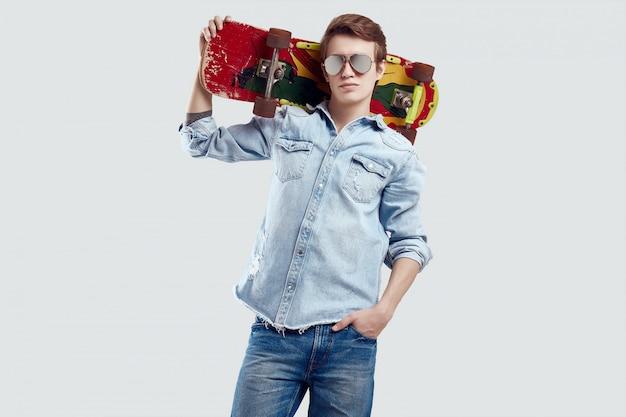 Hippie-mann in der sonnenbrille und in jeansjacke, die mit skateboard aufwerfen Premium Fotos