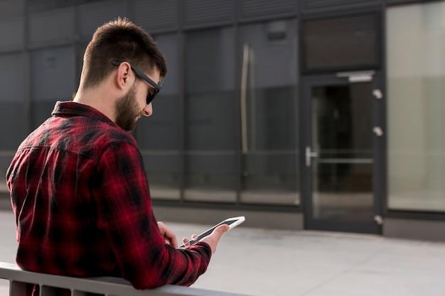 Hippie mit sonnenbrille unter verwendung des smartphone Kostenlose Fotos