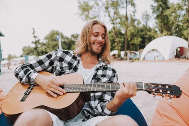 Hippie-musiker, der akustikgitarre auf strand spielt Premium Fotos