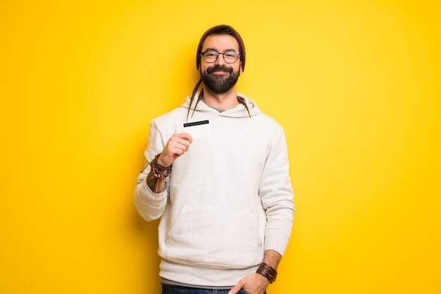 Hippiemann mit den dreadlocks, die eine kreditkarte halten Premium Fotos
