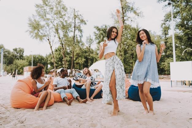 Hippies, welche die gitarre singt das tanzen auf strand spielen Premium Fotos