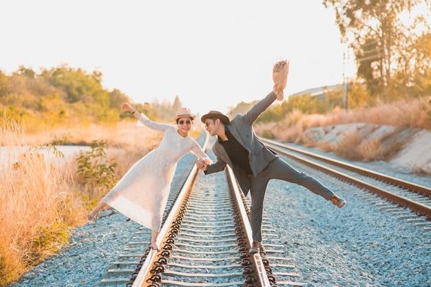 Hipster braut und bräutigam fühlen sich glücklich lächelnd und lachend, während sie auf eisenbahn gehen Premium Fotos