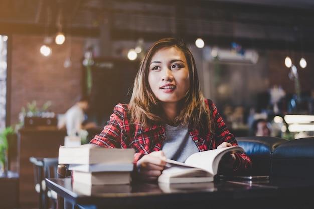 Hipster frau teenager sitzen genießen lesebuch im café. vintage filter getönt. Kostenlose Fotos