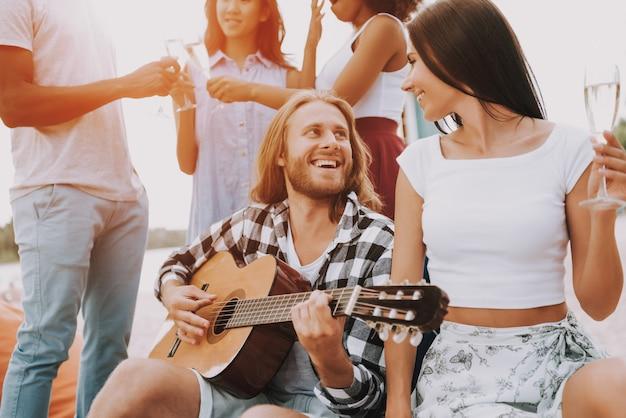 Hipster-freunde, die gitarre spielen und singen. Premium Fotos
