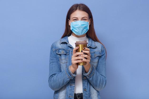 Hipster-mädchen in der medizinischen gesichtsmaske und in der jeansjacke, die kaffee vom thermobecher trinken Kostenlose Fotos