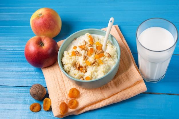 Hirsemilchbrei mit apple, walnuss und getrockneten aprikosen auf einem hölzernen blauen hintergrund Premium Fotos