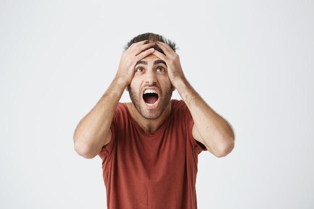 Hispanic bärtiger mann im roten hemd ausdrucksstark reagieren auf schlechte nachrichten von der arbeit, die über seinen chef sauer werden. unglücklicher kerl, der schreit, vom job gefeuert zu werden. Kostenlose Fotos